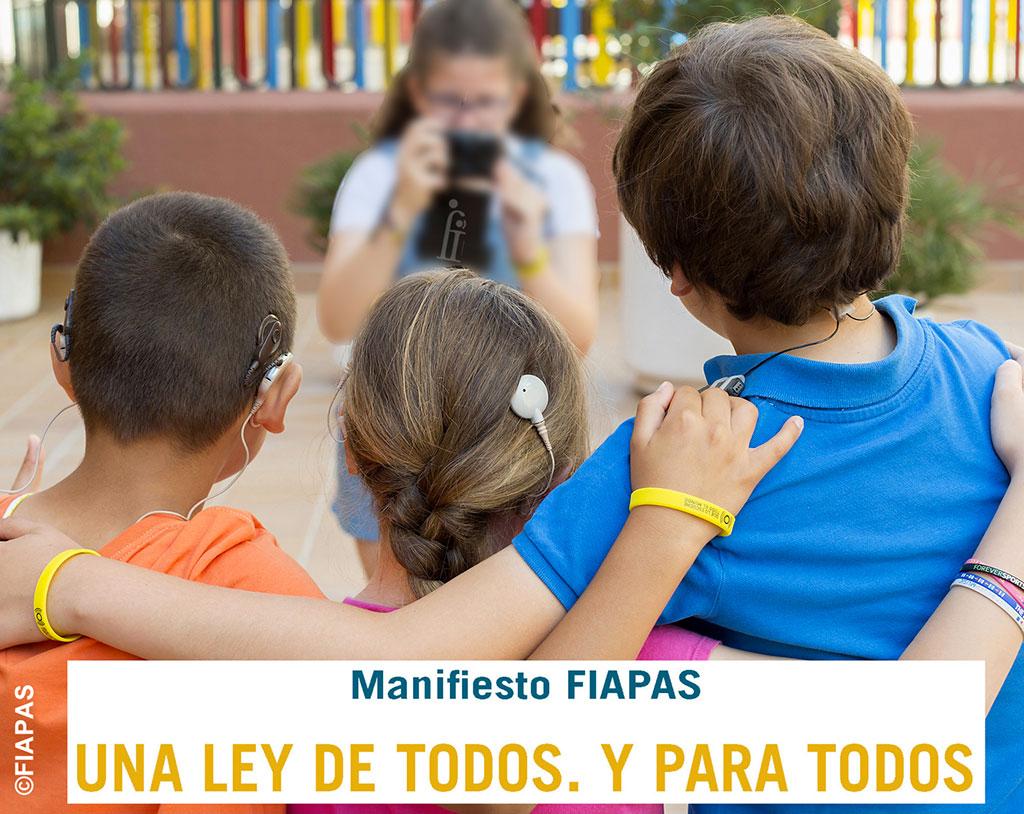 tres niños con prótesis auditivas haciéndose una foto