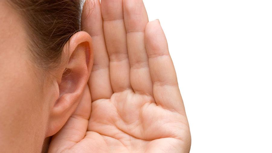 mujer con mano en oído para escuchar mejor