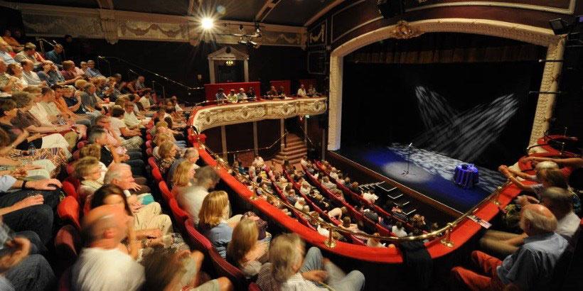 Interior de un teatro lleno de gente