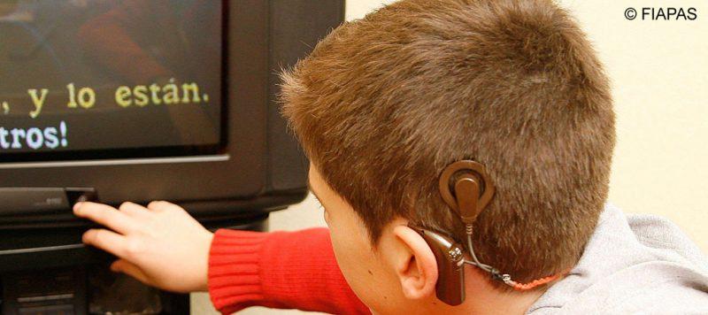 Niño con implante frente a una televisión en la que aparecen subtítulos