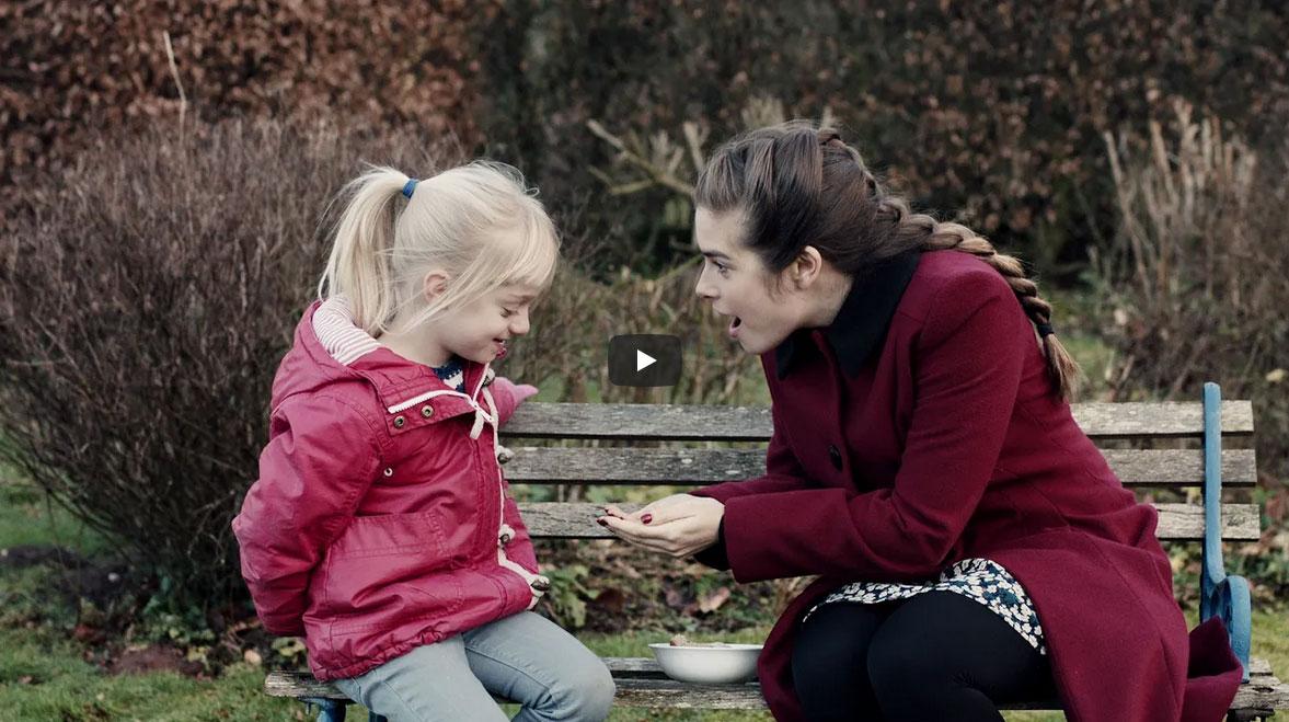 Mujer enseñando algo en las manos a una niña sorda