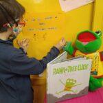 Niño pintando una cartulina. Aparece un cuento y una rana peluche.