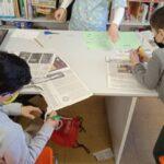 Niños en la biblioteca recortando papelería