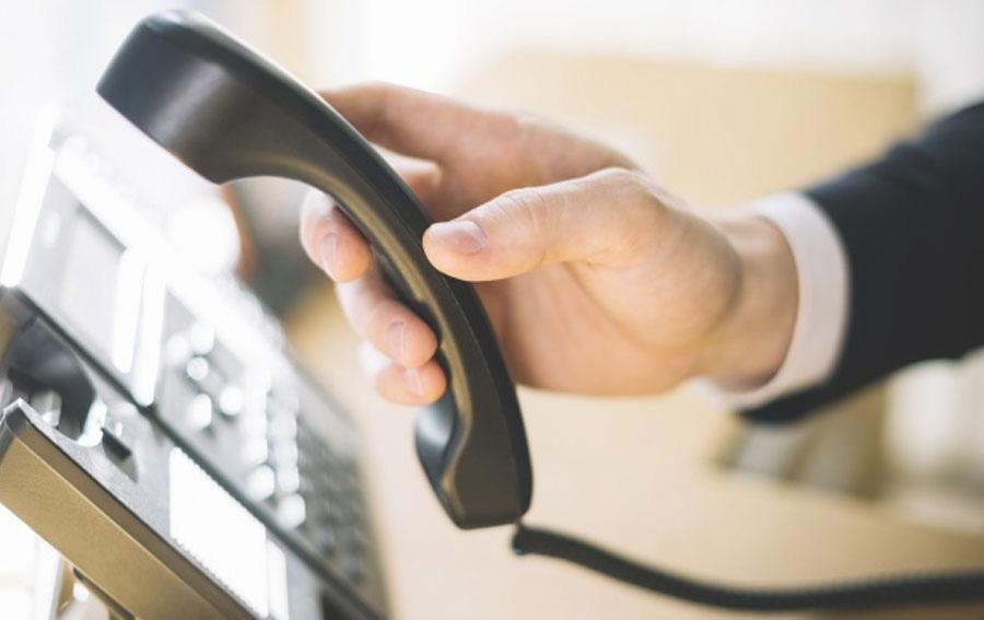 Mano descolgando un teléfono